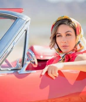 Woman with a colored scarf in a red car posing for a photo portrait