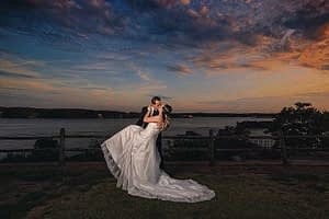 Wedding picture of a couple posing with a beautiful sunset behind them
