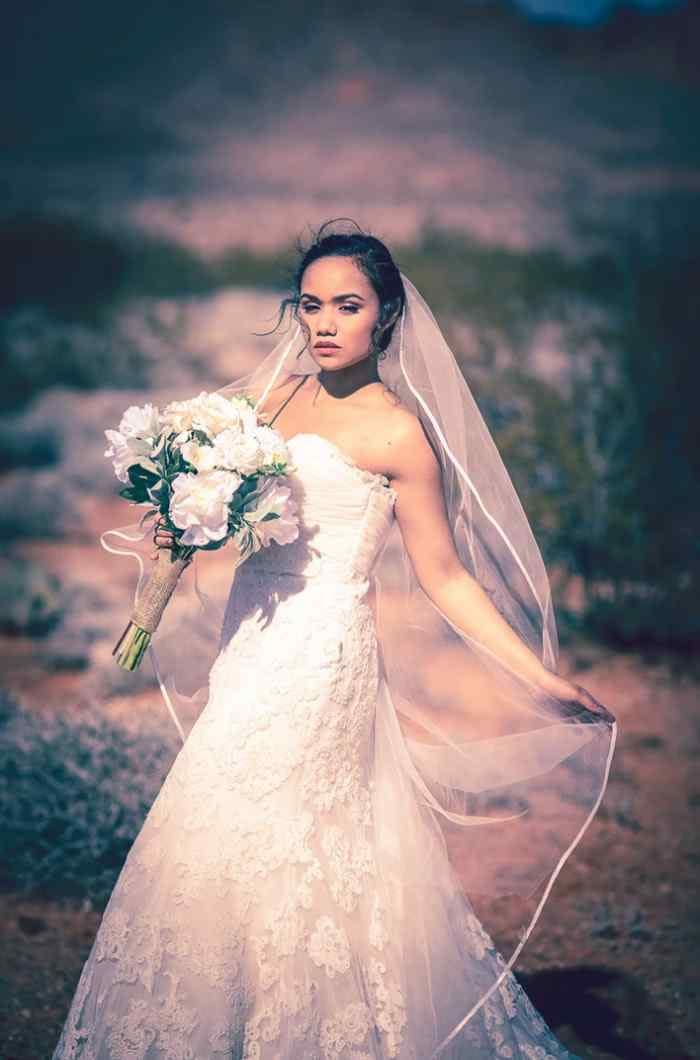 Bride with bouquet and flowing veil posing for wedding pictures