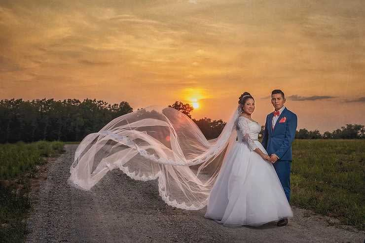 Wedding photoshoot with couple at sunset and the bride's train flowing in the breeze