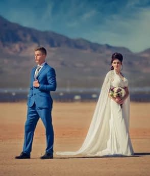 Young couple at a wedding photography session in the desert with mountains in the background