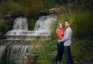 Couple posing for engagement photo beside a waterfall