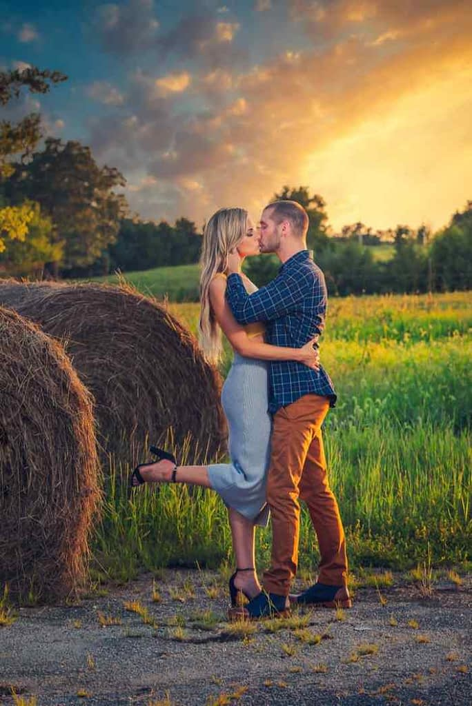 Couple in an engagement photo shoot in a hay field by some big bales of hay