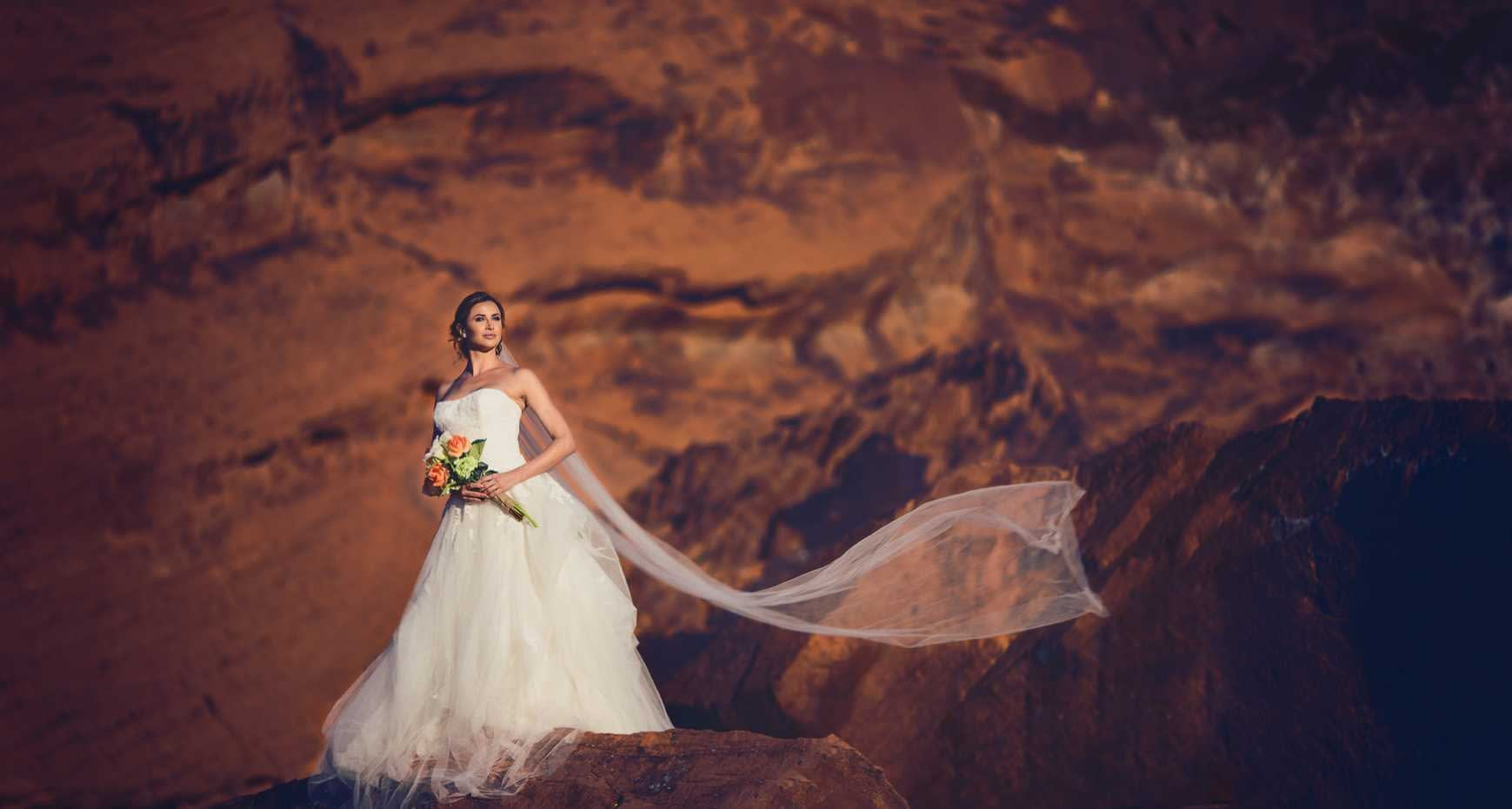 Dramatic bridal shot with flowing veil in the mountains by wedding photographers